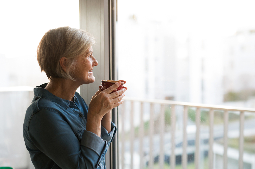 A senior looking out her apartment window.